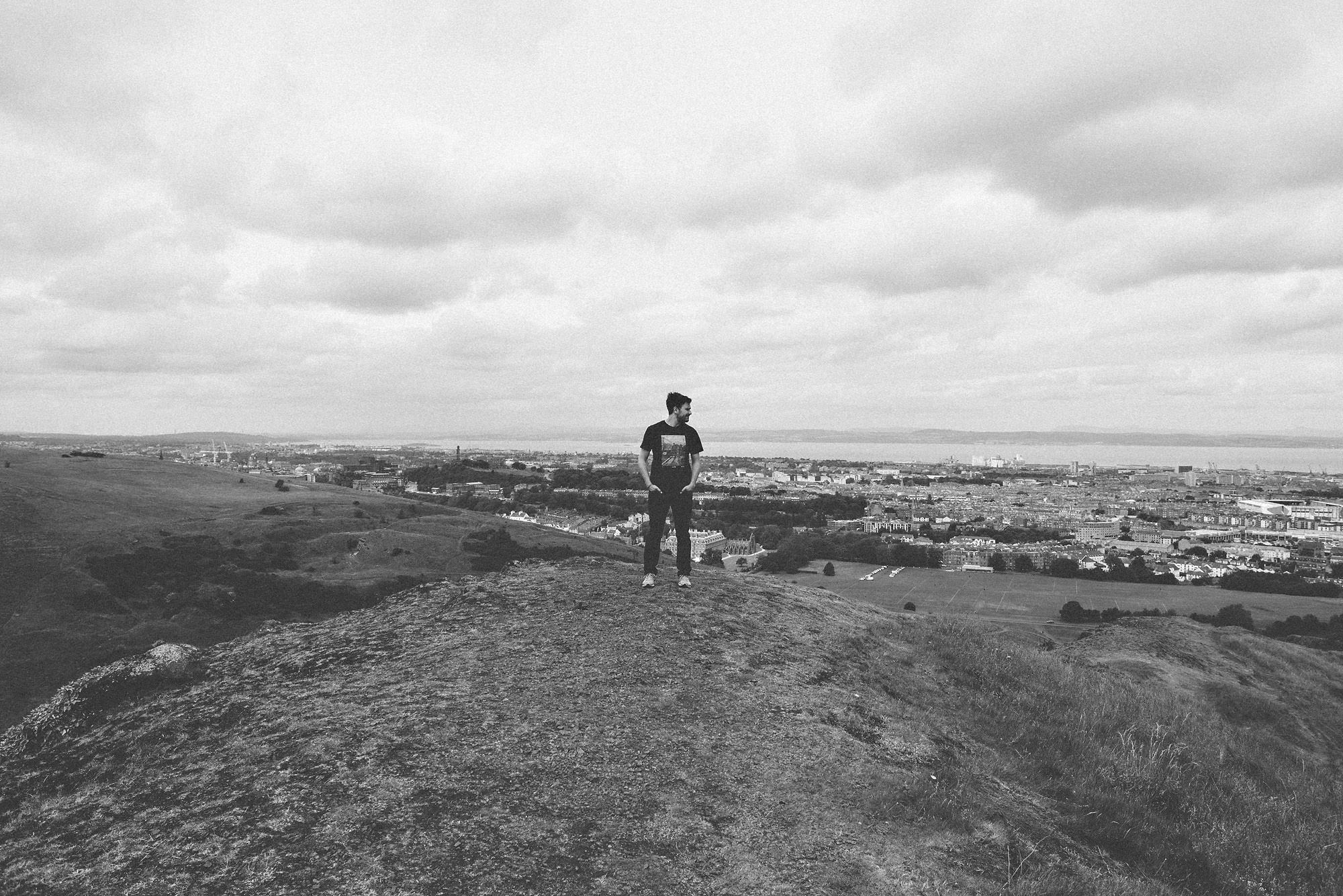 Callum Pinkney Photographer posing at Arthur's Seat in black and white