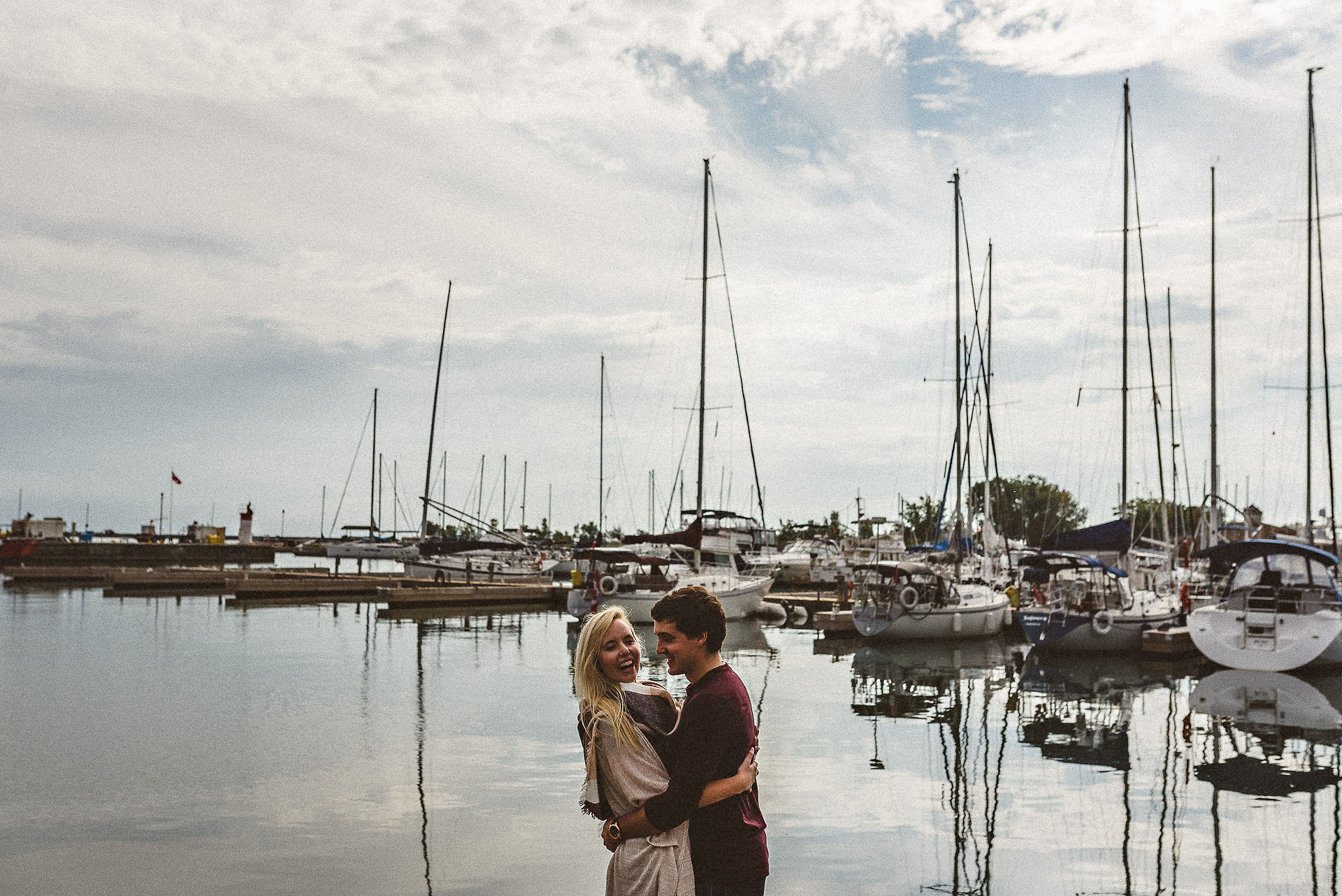 couple laughing in front of boats at cobourg engagement session
