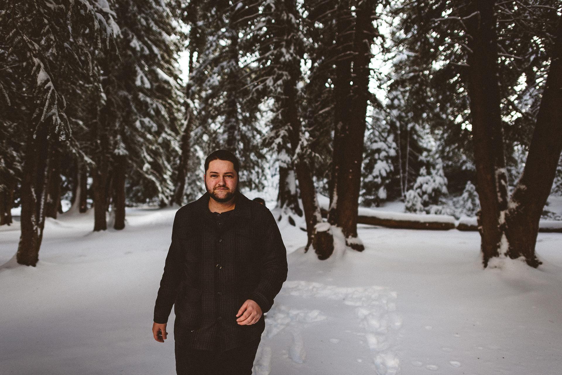 guy walking in snowy tree line