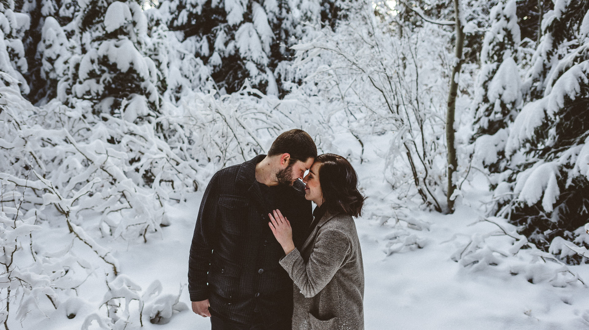 couple embracing in front of snow