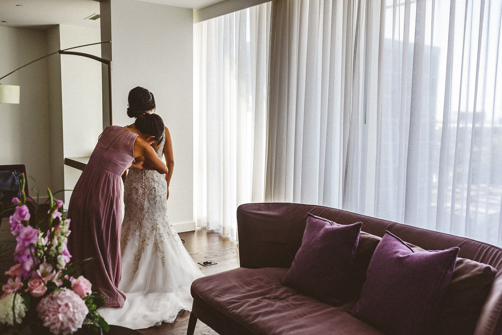 Bride getting help from bridesmaid with dress