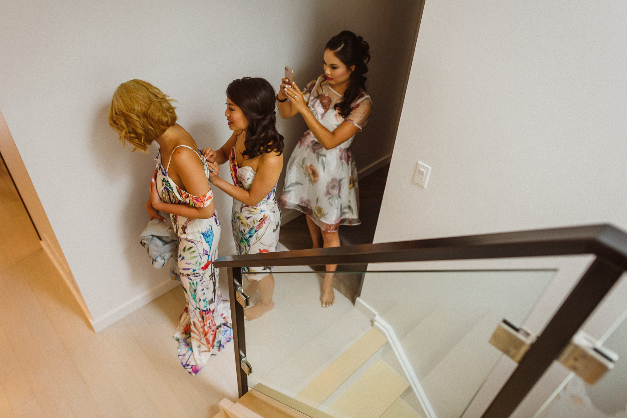 bridesmaids helping each other get dressed