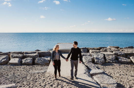 couple walking on beach at Fun and Candid Engagement Session at Woodbine Beaches in Toronto