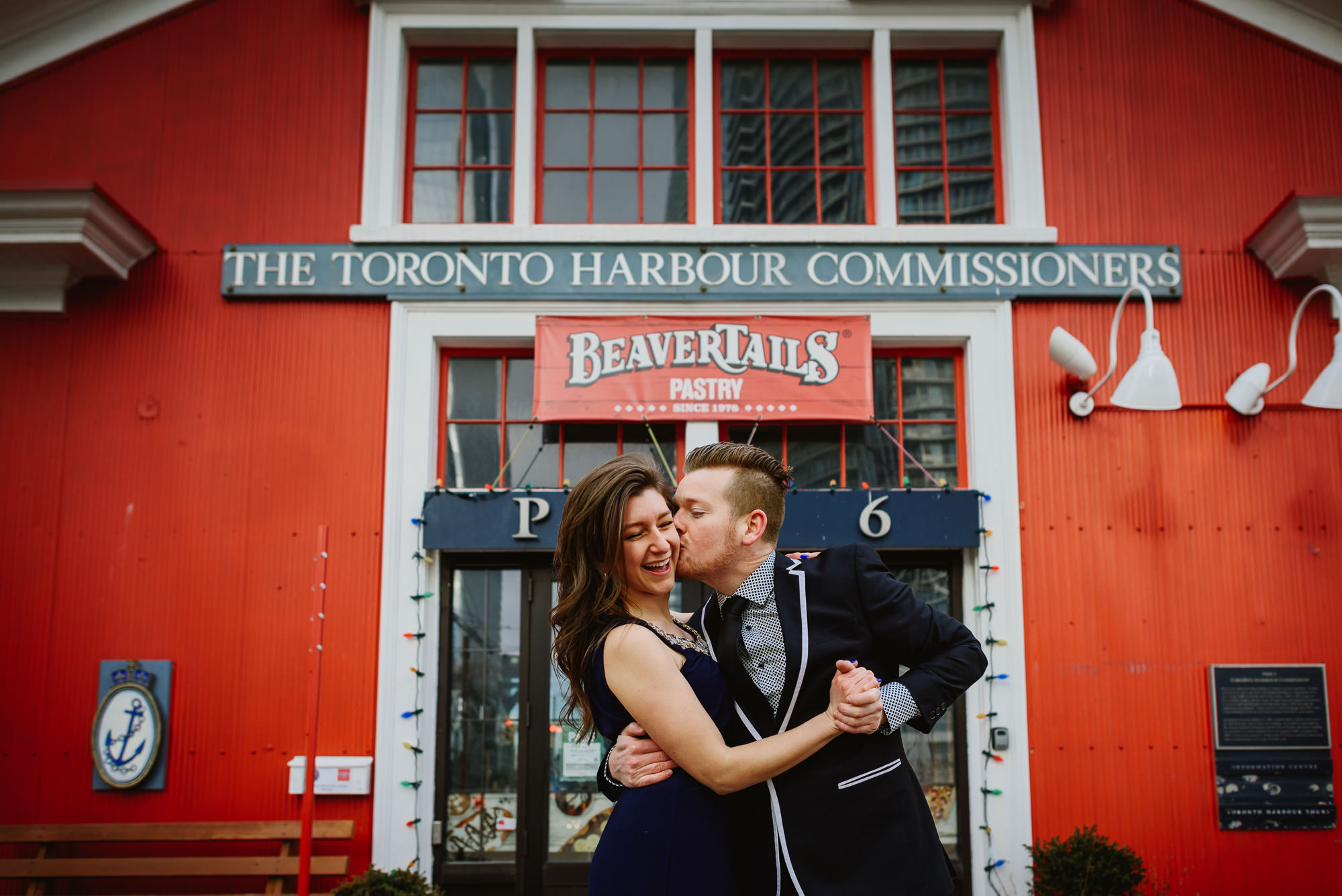 Man kissing woman during fun and energetic harbourfront engagement session in Toronto